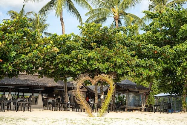 Dom na plaży w pobliżu palm z widokiem na piaszczystą plażę