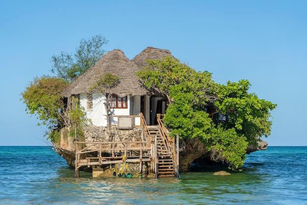 Dom na skale podczas przypływu w wodzie morskiej na wyspie zanzibar