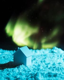 Dom na śniegu z zorzą polarną