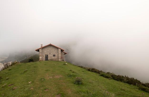 Dom na wsi na górze otaczającej mgłą