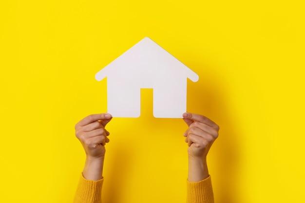 Dom na żółtym tle trzymając się za ręce, koncepcja inwestycji w nieruchomości