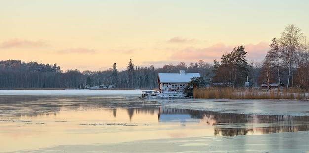 Dom nad brzegiem lodowatego bałtyku o zachodzie słońca.