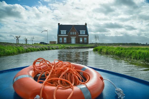 Dom nad brzegiem rzeki. widok z łodzi podróżnej. park kwiatowy keukenhof.