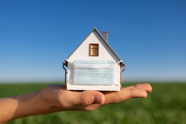 Dom noszenie w ręku maski ochronnej przed wiosennym zielonym polem i błękitną powierzchnią nieba