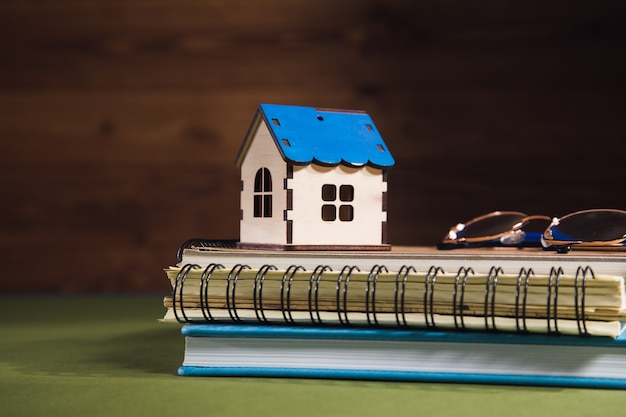 Dom, okulary i notatnik na stole