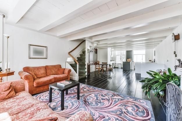 Dom oświetlony słońcem, wyposażony w sofy z terakoty i ozdobny dywan na drewnianej podłodze w pobliżu schodów prowadzących na drugie piętro