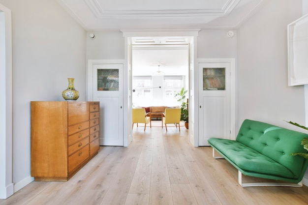 Dom przechodzi przez salon ze stylową szarą kanapą i drewnianą komodą przy wejściu do salonu