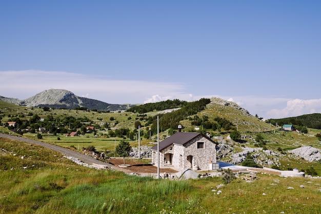 Dom przy drodze w wysokogórskiej wsi wśród drzew ziół i zieleni