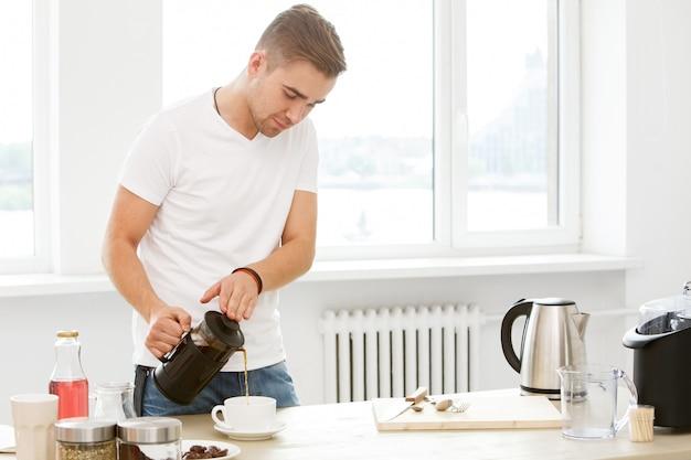 Dom, rano. człowiek z filiżanką kawy