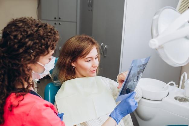 Dom rodzinny dentysta pokazuje zdjęcie rentgenowskie. młoda kobieta siedząca na przyjęciu w pobliżu dentysty. dziewczyna dentysta
