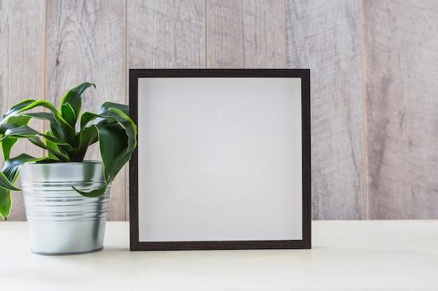 Dom roślin w srebrnym pojemniku z ramką obrazu na białym biurku