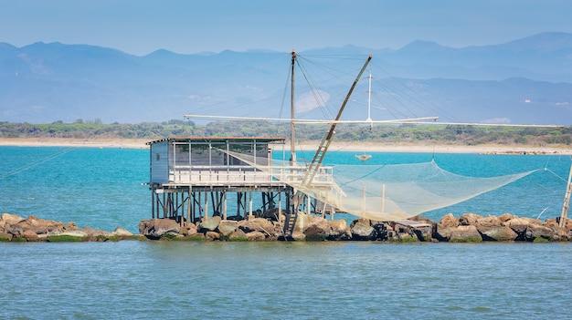 Dom rybacki woden i sieć z widokiem na morze w marina di pisa, toskania, włochy