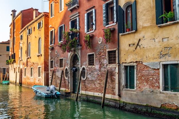 Dom starożytnej tradycyjnej architektury i zacumowane łodzie na kanale w wenecji