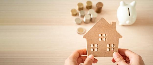 Dom trzymany w rękach kobiety planującej zaoszczędzić pieniądze na inwestycje w nieruchomości. do oszczędzania lub inwestowania w dom.