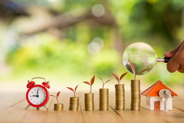 Dom umieszczony na monetach męska ręka planuje oszczędności pieniędzy na zakup domu koncepcji koncepcji drabiny nieruchomości, inwestycji hipotecznych i nieruchomości. za oszczędność lub inwestycję w dom,