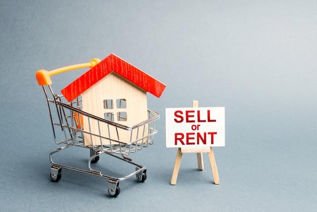 Dom w koszyku i stojaku z napisem sprzedam lub wynajmę wynajem lub sprzedaż domu