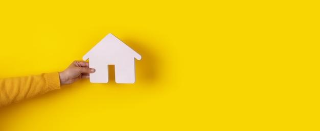 Dom w ręku na żółtym tle, koncepcja kupna domu na kredyt, makieta panoramiczna