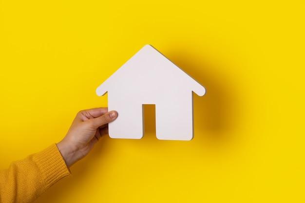 Dom w ręku na żółtym tle, koncepcja kupna domu na kredyt