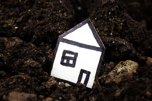 Dom w ziemi, wpadający w pęknięcie w ziemi. pojęcie trzęsienia ziemi i utraty domu. zadłużenia kredytowe.