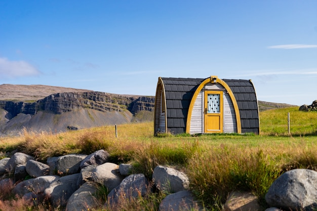 Dom wiejski na wzgórzu na islandii z zachmurzonym niebem i ładnym widokiem