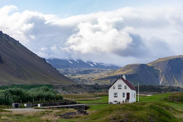 Dom wiejski na wzgórzu w islandii z zachmurzonym niebem i ładnym widokiem na tle