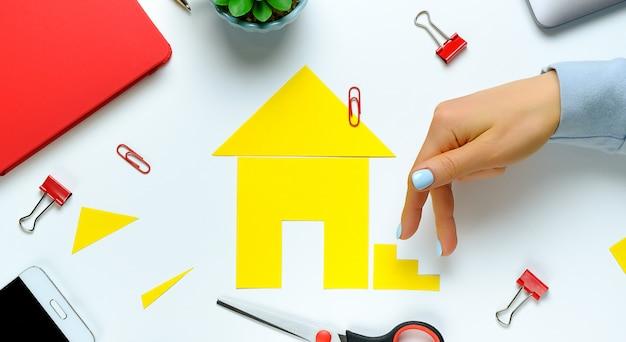 Dom wycięty z kolorowego papieru. palce kobiety wspinają się po schodach. koncepcja realizacji marzenia o posiadaniu domu, kupowaniu i budowaniu mieszkań. transparent.