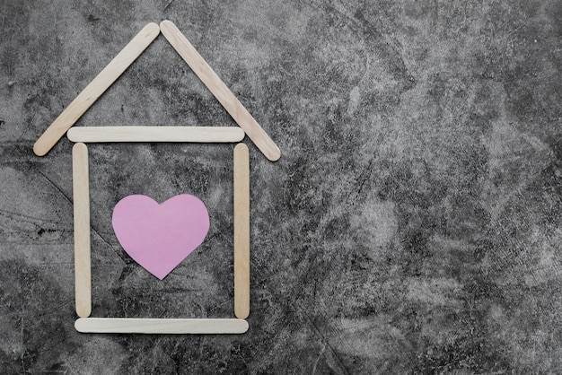 Dom wykonany z drewnianych pałeczek do lodów o kształcie serca na czarnej ścianie grunge