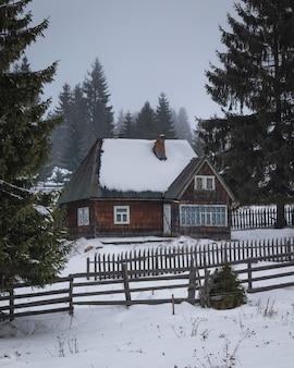Dom z drewnianym płotem pośrodku śniegu i sosen
