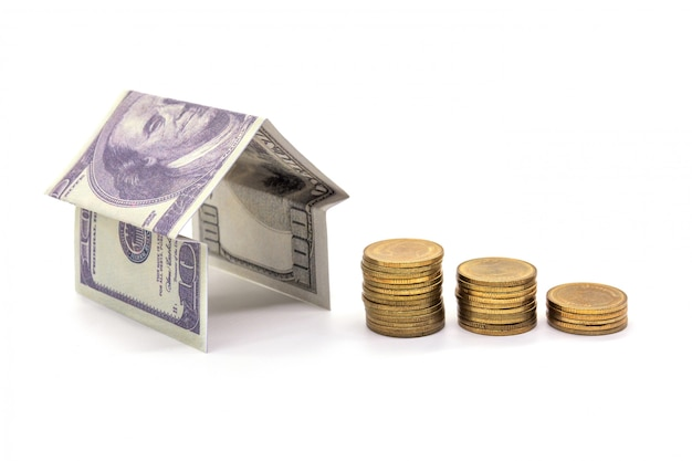 Dom z gotówki dolarowy pieniądze odizolowywający na bielu