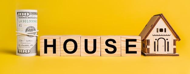 Dom z miniaturowym modelem domu i pieniędzmi na żółtym tle. pojęcie biznesu, finansów, kredytu, podatków, nieruchomości, domu, mieszkania