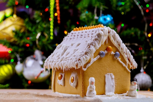 Dom z piernika na światłach chrismtas ozdobiony drzewem