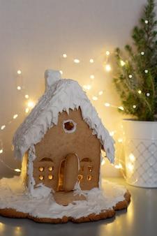 Dom z piernika na tle rozmazanych światełświąteczna koncepcja żywności świątecznej