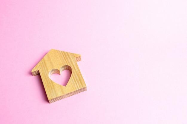 Dom z sercem na różowym tle