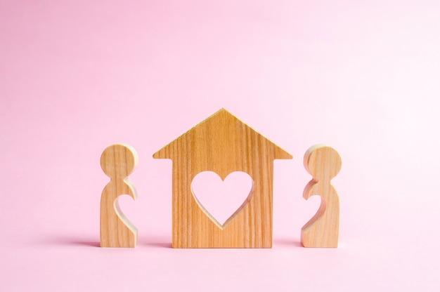 Dom z sercem stoi między parą miłości