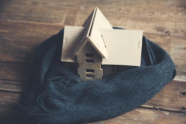 Dom z szalikiem na drewnianym stole