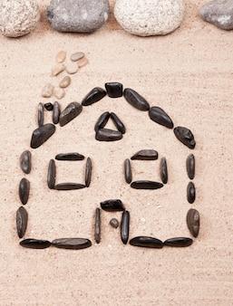 Dom zaprojektowany z kamykami na piasku plaży