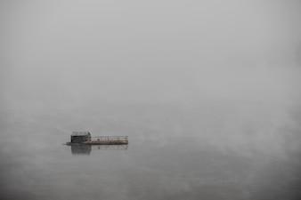 Domek na łodzi i mgliste jezioro