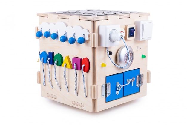 Domek z drewna - zabawka edukacyjna dla dzieci, niemowląt na białym, składająca się z wielokolorowych drewnianych puzzli, labiryntu, sprzętu, sortera, przełączników, gniazd, żarówki, przełącznika