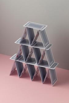 Domek z kart na różowym tle