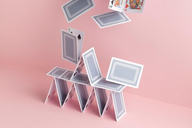 Domek z kart spada na różowym tle
