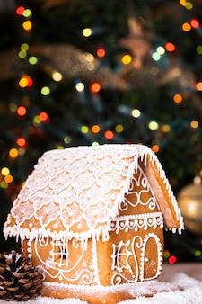 Domek z piernika nad nieostrymi światłami ozdobionej jodły chrismtas