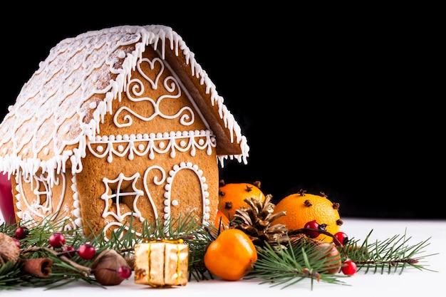 Domek z piernika z dekoracjami świątecznymi na białym tle