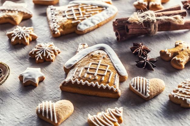 Domek z piernikami i innymi ciasteczkami świątecznymi wraz z cynamonem i szyszkami sosnowymi.