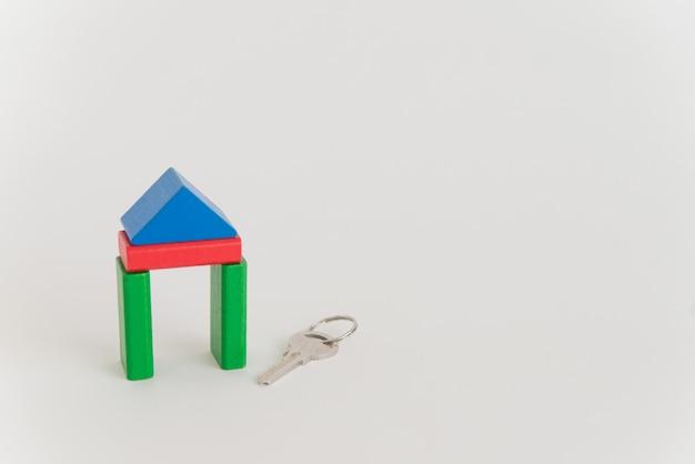 Domek z zabawkami i prawdziwy metalowy klucz na białej przestrzeni