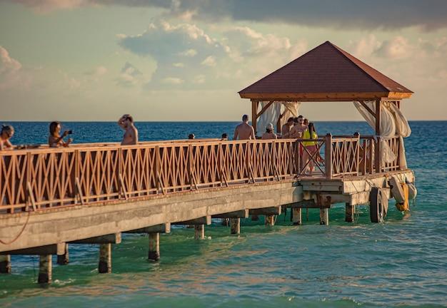 Dominicus, dominikana 6 lutego 2020: ludzie chodzą po molo dominicus o zachodzie słońca