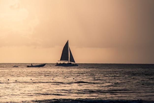 Dominika zachód słońca z łodzią na morzu na horyzoncie