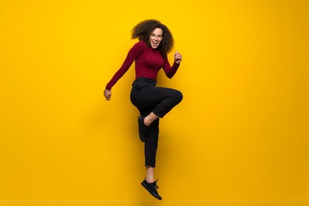 Dominikańska kobieta skacze nad odosobnioną kolor żółty ścianą z kędzierzawym włosy
