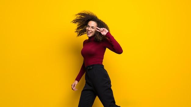 Dominikańska kobieta z kędzierzawym włosy doskakiwaniem na kolor żółty ścianie