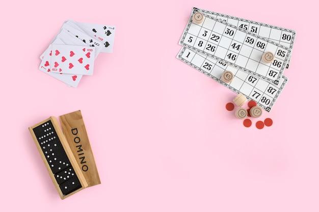 Domino, karty do gry i lotto na różowej ścianie, widok z góry. gry planszowe dla rodziny