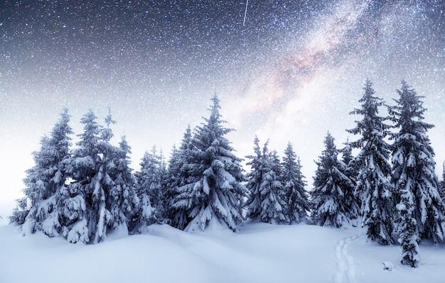 Domki w górach w nocy pod gwiazdami. dzięki uprzejmości nasa. magiczne wydarzenie w mroźny dzień.